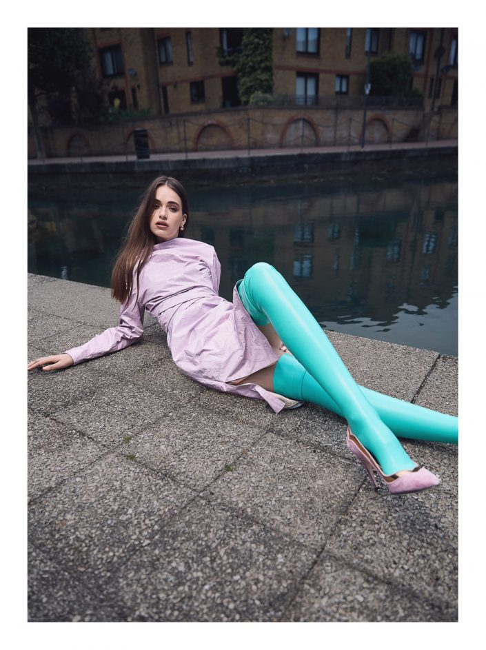 girl laying with purple dress shoes and legging