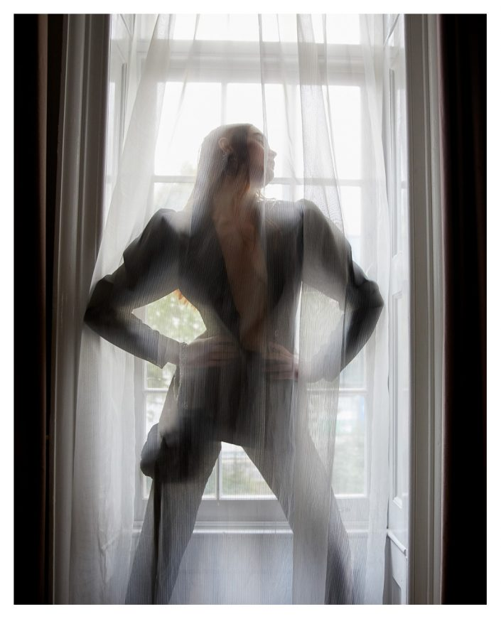 girl posing behind the curtain in hotel room