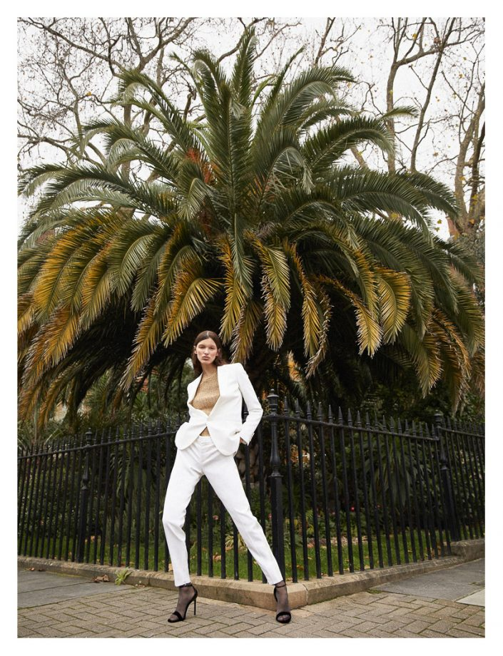 girl with white suit front on palm tree