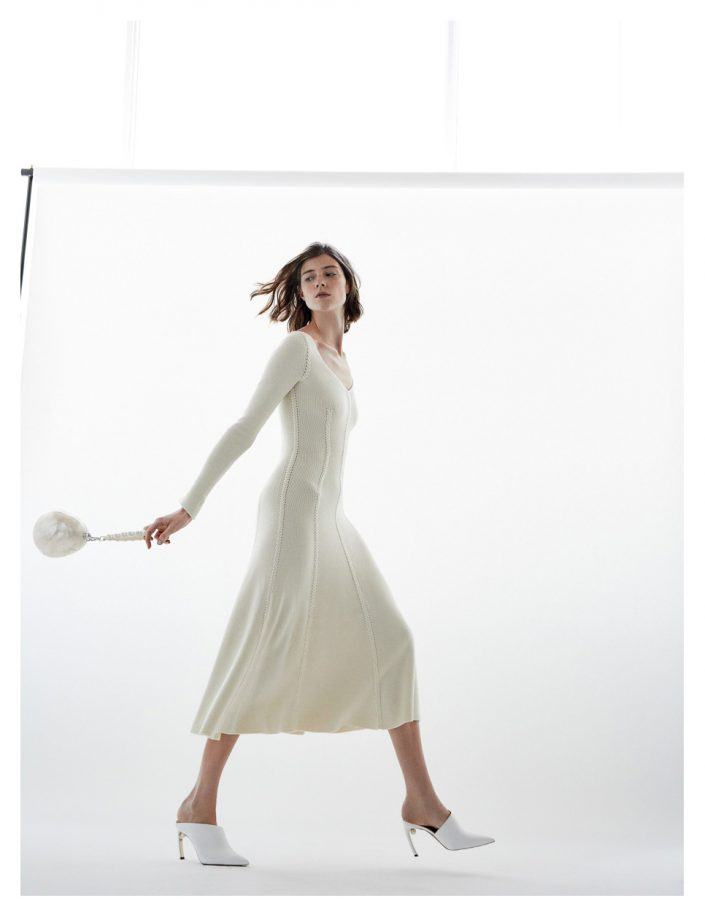 Girl is walking with white dress shoes and purse in studio white background
